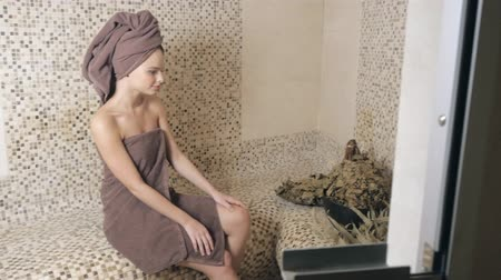 mosás : Attractive woman relaxing in a hammam - turkish steam bath with ceramic tile in roman style Stock mozgókép