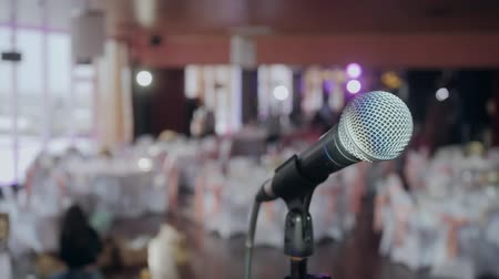 общественный : Microphone over the Abstract blurred conference hall or wedding banquet background Стоковые видеозаписи