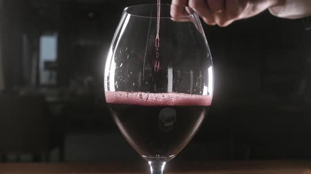 bica : Bartender pours red wine in glass from big transparent vessel Stock Footage