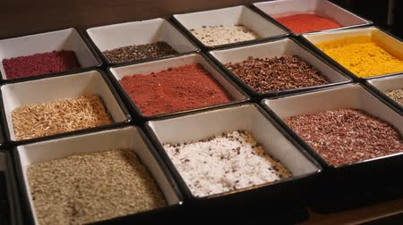 seasonings : vintage wooden box, with many compartments, filled with spices, over old wooden table, sprinkled with spices, abstract compositions,