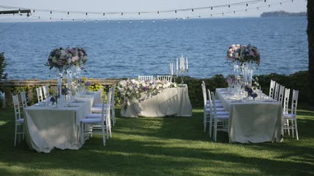 служить : Beautiful table setting with crockery and flowers for a party, wedding reception or other festive event. On the shores of lake Garda, Italy.