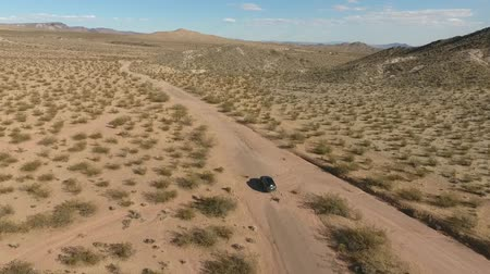 birdseye : Flight over long highway at monument valley in Utah - Drone Aerial over cars in Arizona. Top view drone footage flying over dry and beige desert, drought resulted landscape, global warming threat