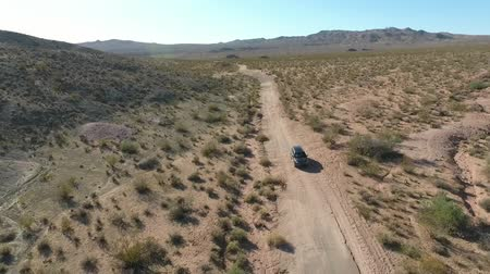 wilderness area : Flight over long highway at monument valley in Utah - Drone Aerial over cars in Arizona. Top view drone footage flying over dry and beige desert, drought resulted landscape, global warming threat