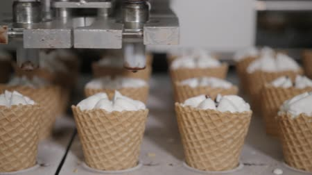 gyártó : Robot machine Automatically pours ice cream and chocolate in a Wafer cups. The conveyor automatic lines for the production of ice cream cones. Wafer cups and cones. Large industrial production. Stock mozgókép