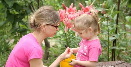 dut : Happy family. Young mother and little daughter eat Tasty, appetizing berries mulberry. They sit in the garden on the background of beautiful flowers. They play, laugh, cheerfully, emotionally.