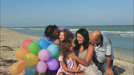 lánya : Happy family. Grandmother, grandfather, Loving mother and youngest daughter and an seventeen-year-old daughter with Down syndrome on the beach With balloons. Positive human emotions, joy.