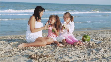 lánya : Happy family. Loving mother and two daughter on the beach With lemonade. One daughter with a disability with Down syndrome. Positive human emotions, feelings. Stock mozgókép