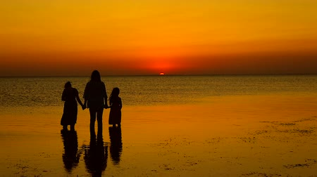 lánya : Happy family. Mother and two daughters standing in the sea. Positive human feelings.