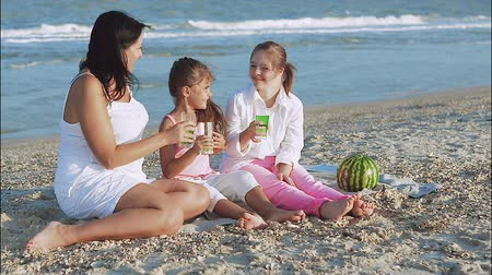 lánya : Happy family. Loving mother and two daughter on the beach With lemonade. One daughter with a disability with Down syndrome. Positive human emotions, feelings Stock mozgókép