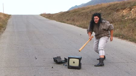 sinir : Woman crashing an old tele receiver with a baseball bat in the middle of the road