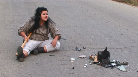 sinir : Woman seating in the middle of a road with a baseball bat near a crashed TV. Fragmented video
