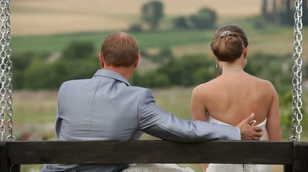 weddings : Newly weds seating on a swing and embracing each other Stock Footage