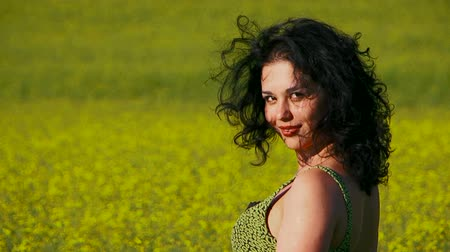kıvırcık : A lovely woman is sitting in a field of Raps and smiling. She dressed in a green sun-dress and have beautiful curly hair. Stok Video