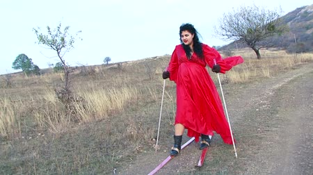 amalucado : Slow motion. Plus-sized crazy woman with long black hair in red dress wearing skis and holding sticks with a wild smile is walking along the footpath in the steppe zone looking really weird. Shot is made at the deserted place at dull day. Stock Footage
