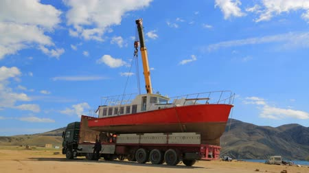 dişli : HOLIDAY CRUISER REMOVAL FOR MAINTENANCE AFTER  HOLIDAY SEASON. KAPSEL BAY NEAR MEGANOM CAPE. October 14th, 2014. This is a locked down video footage of a process of pleasure-boat loading on a truck with the help of crane-machine at the seashore near Kapse Stok Video