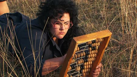 abacus : Shot was captured at the light brown meadow - odd plus-sized woman in black dress wearing glasses moving the beads of the abacus lying on the grass with serious facial expression. Stock Footage
