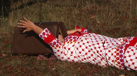 garip : This is a video shot of a weird plus sized  woman in white and red dotted gown lying on the gray faded grass in the meadow with opened suitcase on her head clapping on it with her hands. Side view.