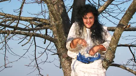 amalucado : This two-framed shot was captured at nature: crazy black haired plus sized woman with a mess on her head and in a long white nightie sitting on a tree and throwing pillow feathers around looking at the camera with a scared and foolish facial expression. B