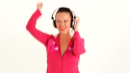 только один человек : Cheerful pretty young pretty woman with dark hair in pink cardigan wearing headphones listening to music and dancing. Waist up studio locked down shot on white background.