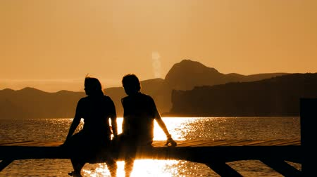 casal heterossexual : Picturesque footage of beautiful sunset on the beach and silhouette of man and woman sitting on the bridge and swinging legs.
