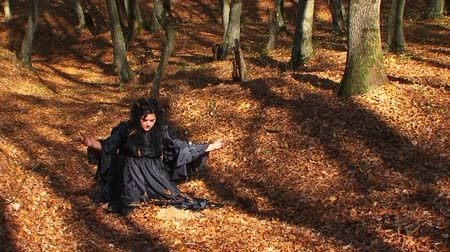 holding onto : Three frames. This is a video of a plus-sized dark haired woman in long black dress sitting on the ground in autumn forest and throwing faded leaves up where they fall onto her head. Female has a very strange and sad facial expression. The woodland is ill