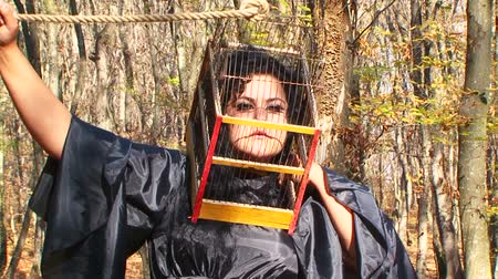 garip : This is a shot of a plus-sized dark haired woman in black dress with a cage on her head holding a rope fixed on the cage above with desperate facial expression. Waist up footage in autumn forest among tree trunks at sunny daytime. Zoom out. Stok Video