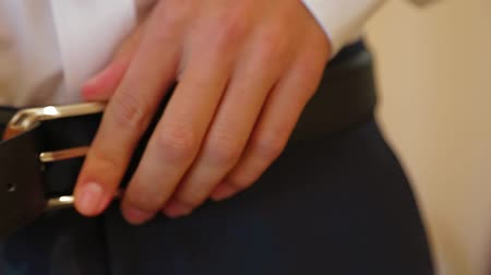 ремень : CLOSE UP: Hands of young man buttoning the belt on his trousers preparing for ceremony.