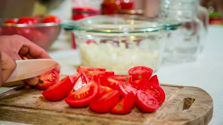prepare food : CLOSE UP: Hands of cook with white knife chopping ripe tomatoes into parts on kitchen board preparing them for mincing.