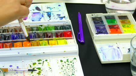 püskül : Several hands together draw and use one palette of watercolors Stok Video