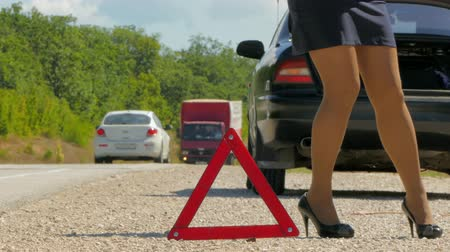 cuidado : a woman walks next to a warning triangle