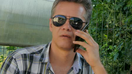 man in black glasses talking on a smartphone