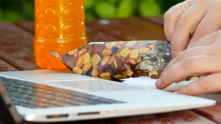 nuez : Trabaja en una laptop y come nueces.