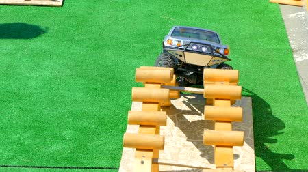 A radio-controlled jeep overcomes an obstacle