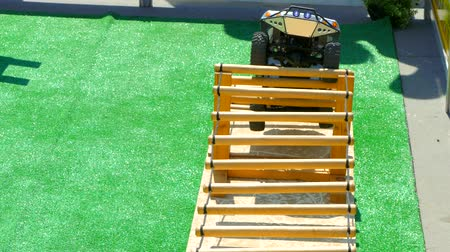 A radio-controlled jeep rises to an obstacle and falls Stok Video