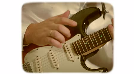 hand is playing on a white electric guitar. 8mm retro style film.