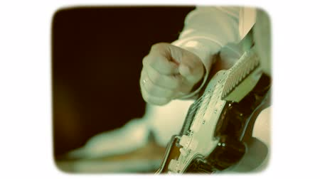 sepia : the hand touches the strings on an electric guitar. 8mm retro style film.