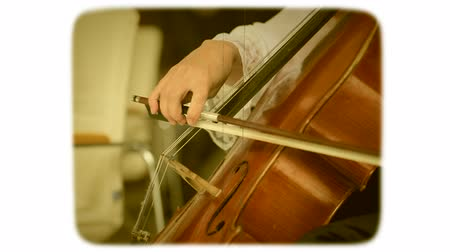 sepya : Female hand with a bow plays on a double bass. 8mm retro style film. Stok Video