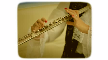 sepya : Female fingers fingering the buttons on the flute. 8mm retro style film.