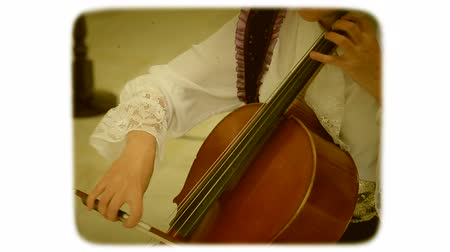 sepia : A woman with a bow drives the strings of a double bass. 8mm retro style film.