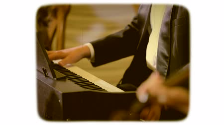 A man in a suit plays the piano. retro style film. 8mm film style.
