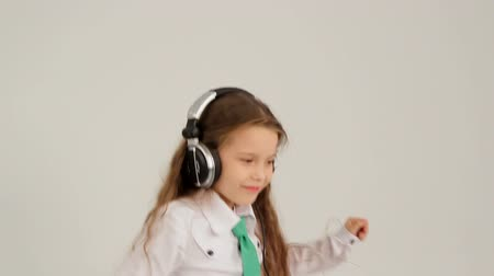Little long-haired girl dancing in headphones. Slow motion.
