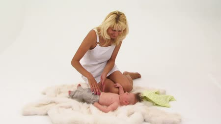 A woman stroking an infant on the floor