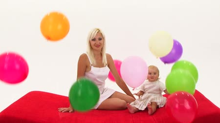 On a woman and a baby a girl falls balloons Stok Video