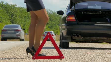tarde : womans legs in heels walk against the warning triangle
