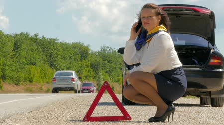 quebrado : woman talking on the phone next to the warning triangle