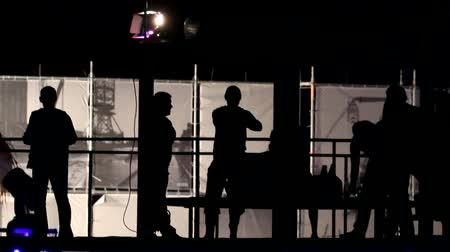 прожектор : Silhouettes of several people dancing on the balcony. Fast moving.