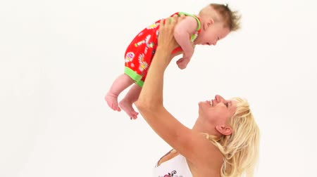 head over : A woman raises a happy baby over her head. Stock Footage