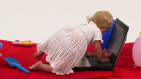 сосать : Baby girl playing with toys and climbing on laptop