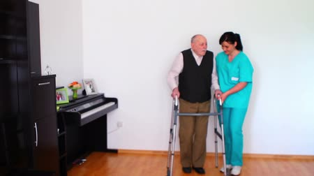 fizjoterapeuta : Carer Helping Elderly Senior Man Using Walking Frame Wideo
