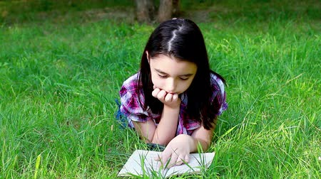 луг : Little girl reading a book Стоковые видеозаписи